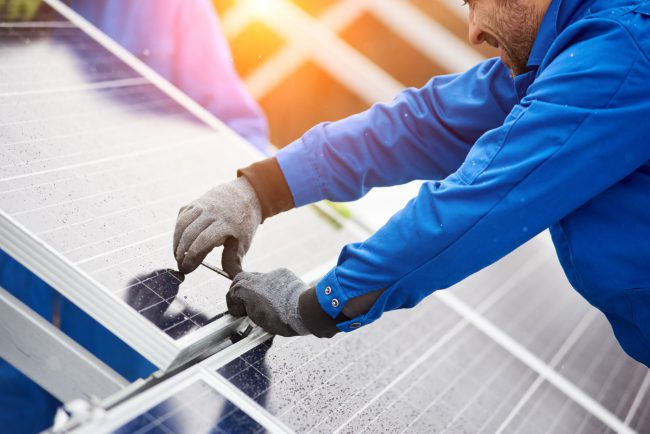 Smiling male technician in blue suit installing photovoltaic blue solar modules with screw. Man electrician panel sun sustainable resources renewable energy source alternative innovation